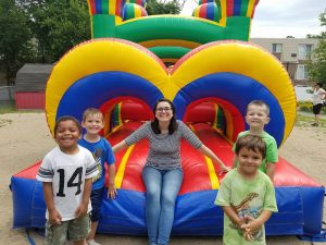 Miss Amanda and four boys at a bouncy castle.