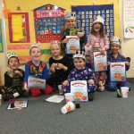 Students display their certificates of completion for 100 days of school.