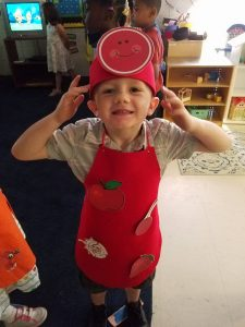 Pre-K student shows off his graduation apron and headgear.