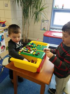 Two boys work at a lego station.
