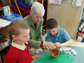 Two boys decorate a flowerpot with their grandmother for Mother's Day.