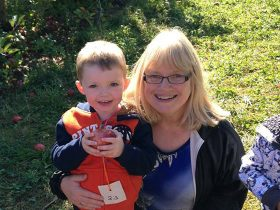 A boy and his mother pose at apple picking.