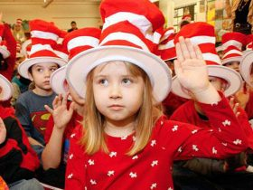 Children in Cat-in-the-Hat hats take a pledge.