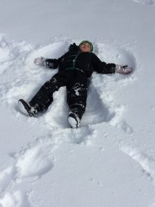 Boy lies in the snow angel he has made.