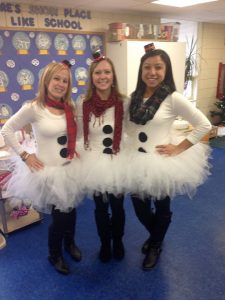 Three staff members dressed in matching snowmen costumes, with tutus.