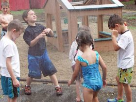 A group of children play in the sprinklers.