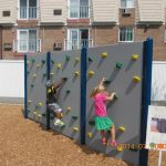 Westbay Children's Center facility exterior: Two children climb the rock wall.