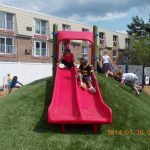 Westbay Children's Center facility exterior: Children play on the slide.